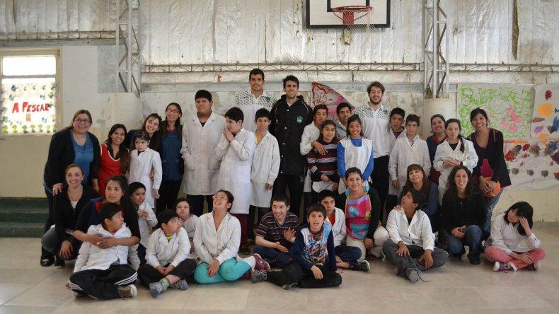 Los jugadores de Gimnasia Indalo junto a los chicos y docentes.