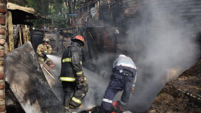Los bomberos combaten el fuego en una de las viviendas siniestradas en el barrio Newbery.
