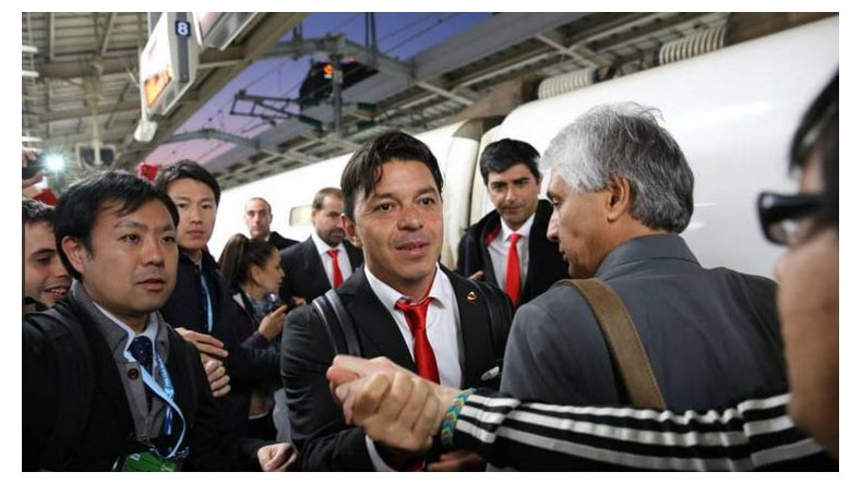 Marcelo Gallardo se saluda con un hincha de River a su llegada en Osaka.