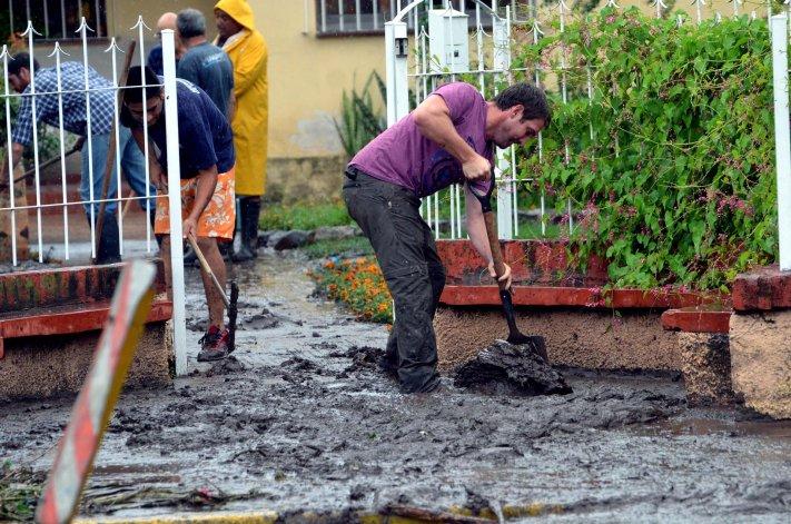 Vecinos de la localidad de Mendiolaza quitan el barro de sus casas producto del fuerte temporal.