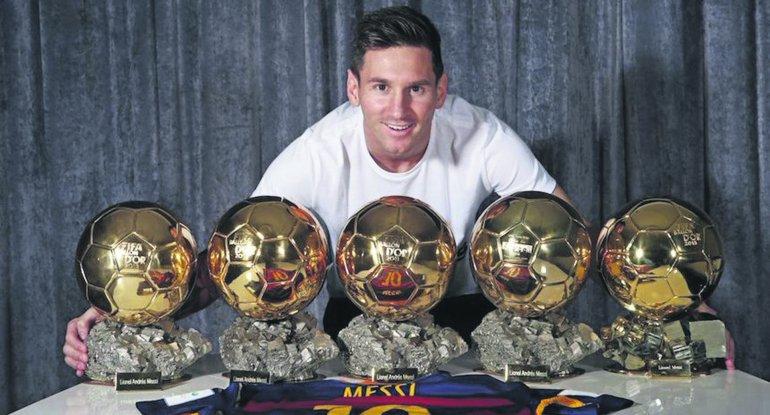 El crack Lionel Messi posa con sus cinco balones dorados.