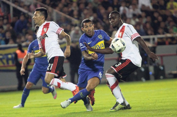 Carlos Tevez ante la marca de Eder Balanta y Leonel Vangioni en el Superclásico jugado hace una semana en Mar del Plata.