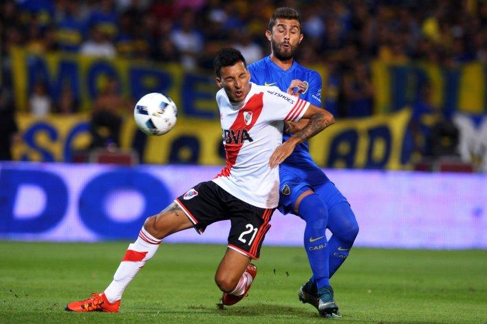 Leonel Vangioni disputa el balón con Gino Peruzzi en el Superclásico que River le ganó anoche a Boca en Mendoza.