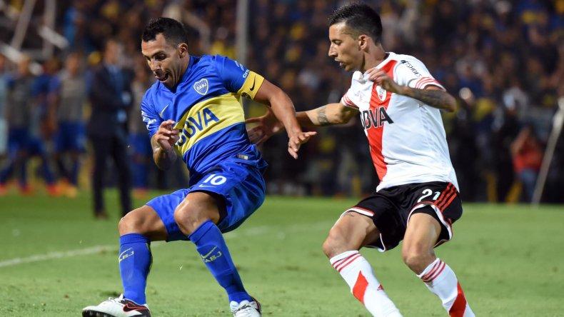 Carlos Tevez con el balón marcado por Leonel Vangioni en el Superclásico que River le ganó a Boca 1-0 en Mendoza.