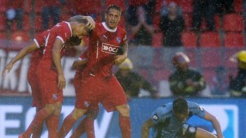 Denis, en su regreso al Rojo, felicita a Rigoni, el autor del gol bajo la lluvia de Avellaneda.