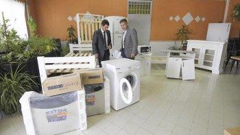 El fiscal de Estado y el actual titular de Lotería observan los objetos que fueron restituidos.