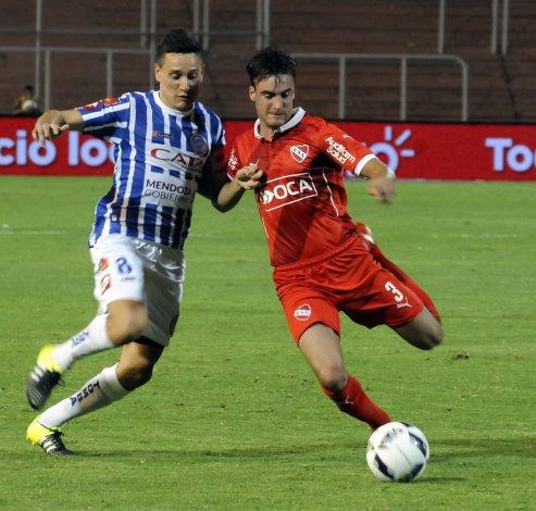 Nicolás Tagliafico y Fernando Zuqui disputan el balón en el partido jugado anoche en Mendoza.