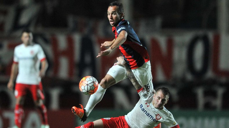 Fernando Belluschi de San Lorenzo trata de eludir la marca de Darío Bottinelli de Toluca.