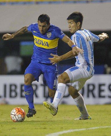 Carlos Tevez se lleva el balón marcado por Luciano Lollo