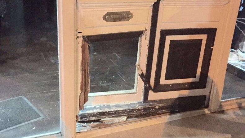 La puerta de madera del local fue destruida a patadas por los delincuentes.