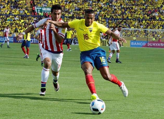 Antonio Valencia se lleva el balón marcado por el paraguayo Darío Lezcano.