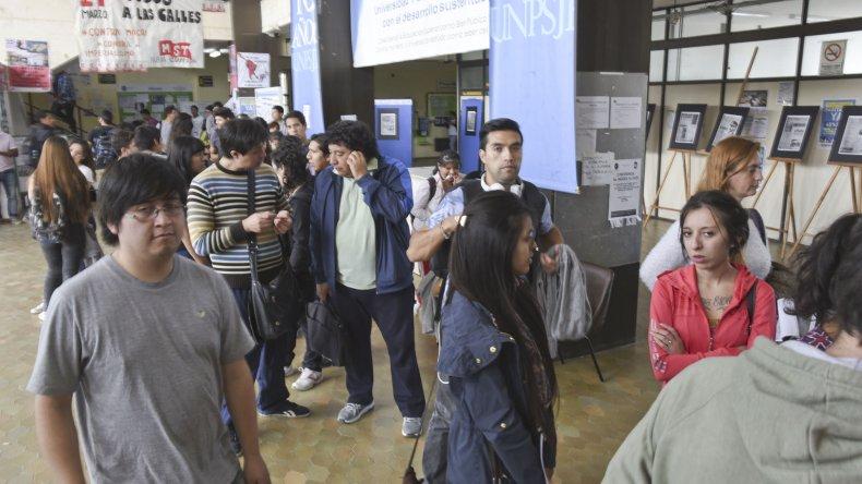 Largas filas de estudiantes a la espera de los bonos se registraban ayer en la Universidad.