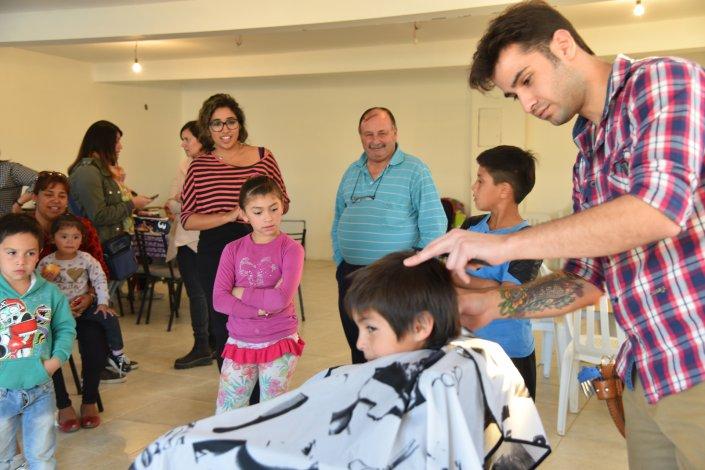 Los más chicos se divierten cuando el coiffeur Marcelo Allende les cambia de look en la sede de la Asociación Civil Manos Amigas.