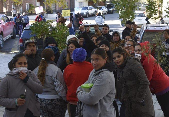 En primer plano se observa a referentes de las familias que tomaron viviendas y ahora exigen servicios básicos. Al fondo