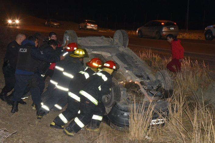Los bomberos dan vuelta el VW Fox para sacarlo de la banquina.