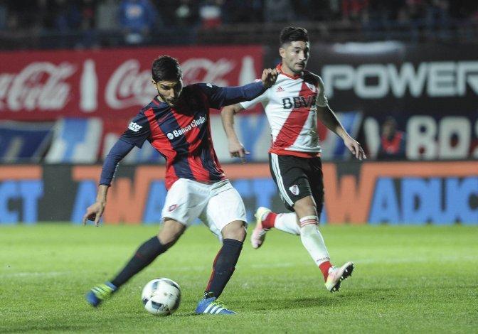 Nicolás Blandi en la acción del segundo gol de San Lorenzo ante la mirada de Milton Casco.