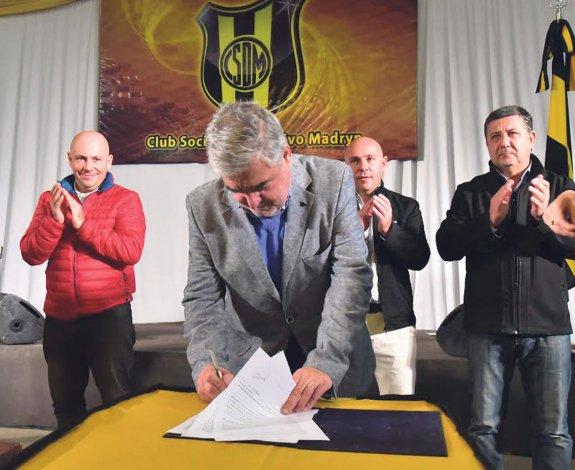 El gobernador firmando convenios en el club Deportivo Madryn que estuvo de cumpleaños.