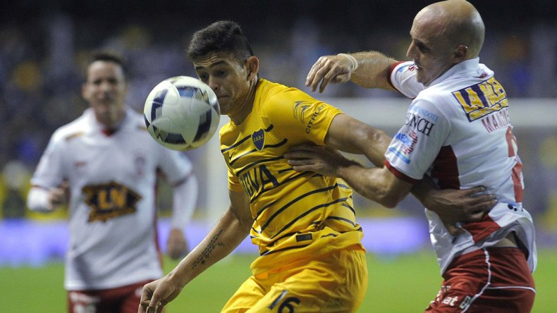 Nicolás Benegas disputa el balón con Federico Mancinelli en el partido que anoche empataron Boca y Huracán en la Bombonera.