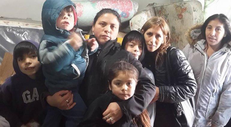 Marcela junto a sus hijos y parte de lo donado.
