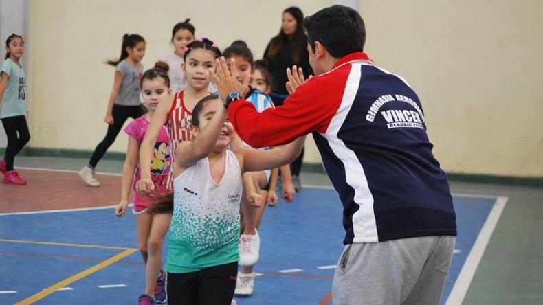 El profesor Pablo Vincen se saluda con una de las pequeñas participantes del módulo de gimnasia aeróbica de competición.