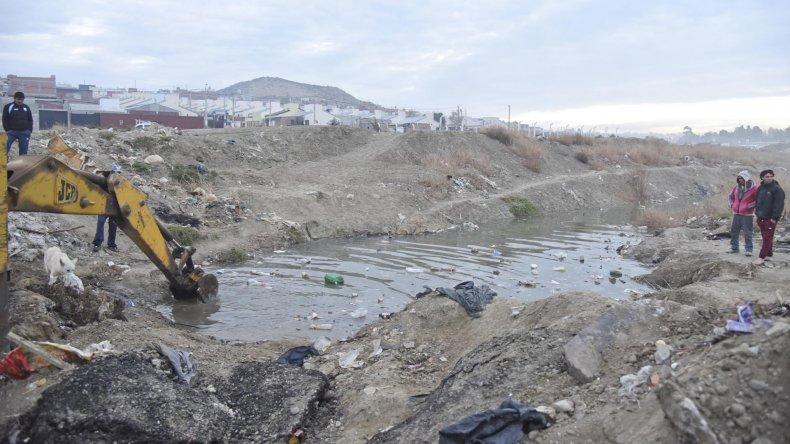 Peligro y contaminación en Berbel y Angelelli. La máquina que contrataron los vecinos intenta quitar la basura que tapa el conducto.