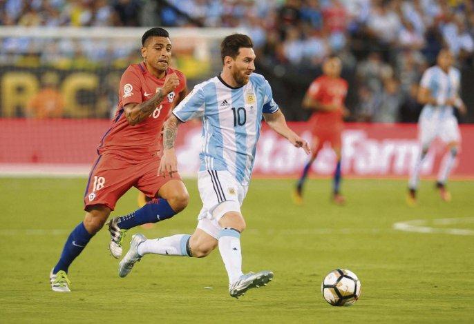 Lionel Messi se lleva el balón marcado por Gonzalo Jara en la final que los chilenos ganaron por penales.
