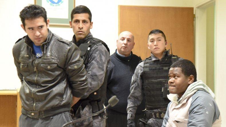 El oficial Pedro Benítez ingresa detenido a la sala de audiencias mientras es observado por Juan Carlos Cuellar Gamboa.