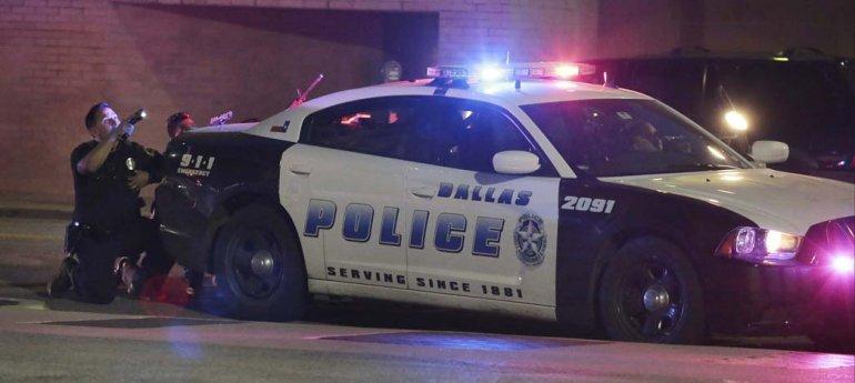 Dos policías se refugian detrás de un patrullero e intentan determinar desde dónde proceden los disparos.