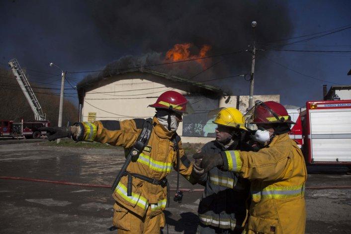 Bomberos custodian el incendio en un depósito de lubricantes.