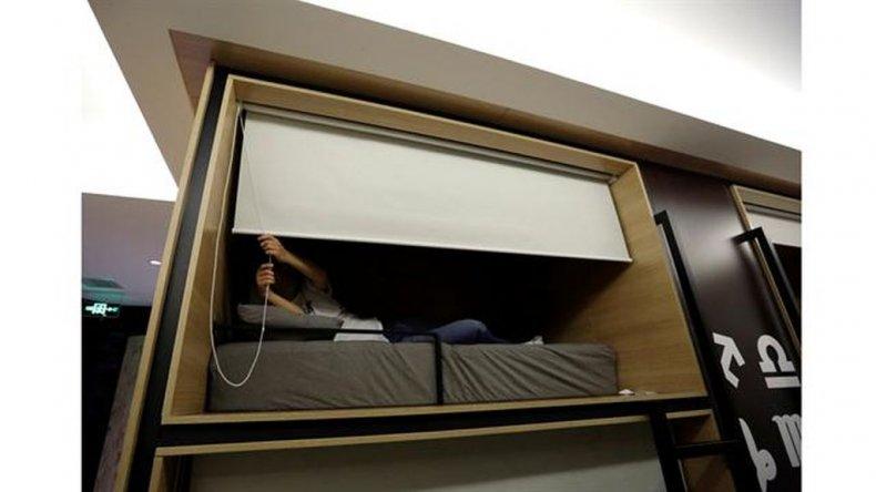 Zhang Shuang Jie, un ingeniero de la empresa Baishan, baja una cortina mientras se prepara para dormir alrededor de la medianoche en un cuarto individual en la oficina.