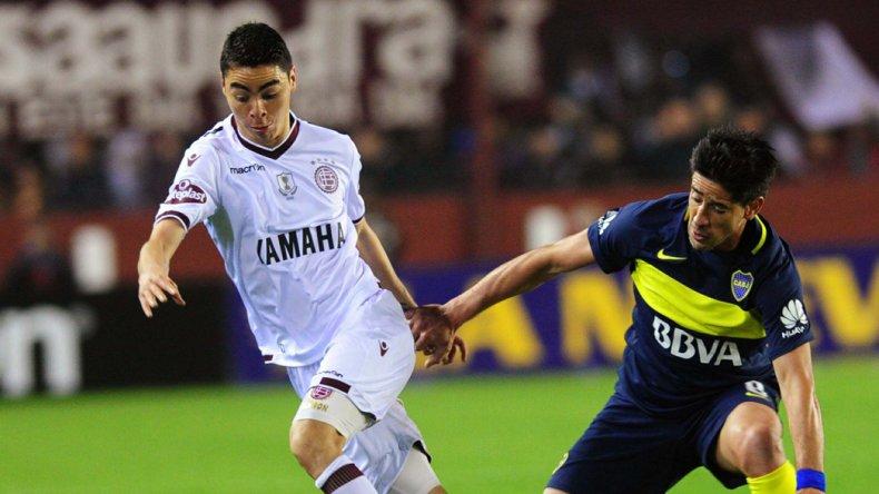 El paraguayo Miguel Almirón con el balón marcado por Pablo Pérez en el partido jugado anoche en cancha de Lanús.