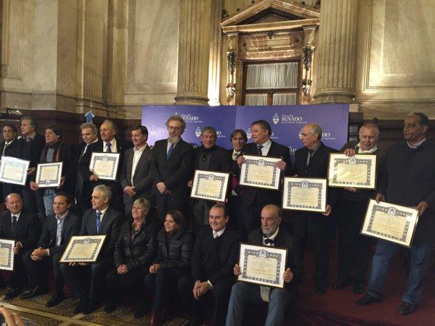 El senador Alfredo Luenzo posa con los homenajeados en el Congreso.