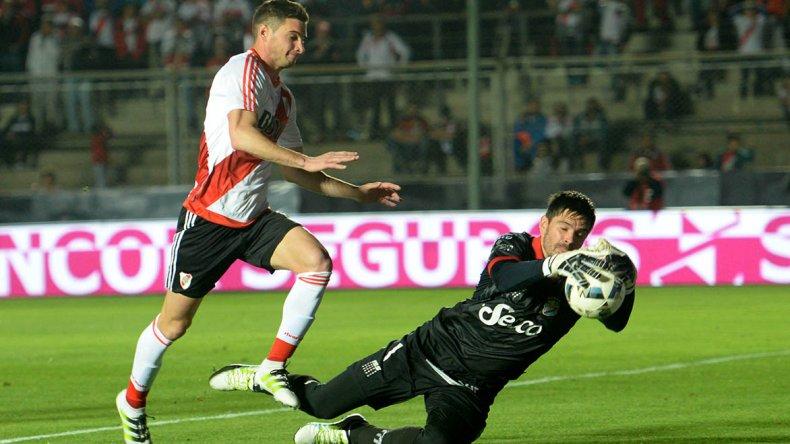 El arquero Fernando Pellegrino se queda con el balón mientras arremetía Lucas Alario.