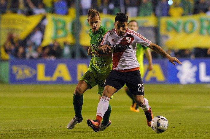 Milton Casco se lleva el balón marcado por Tomás Pochettino en el partido que anoche Defensa y River igualaron 3-3 en Florencio Varela.