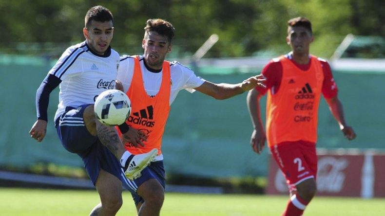 Angel Correa se lleva el balón marcado por Emanuel Mas en la práctica que la Selección realizó ayer.