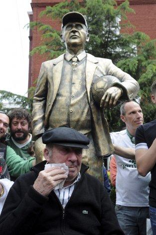 Carlos Timoteo Griguol con un pañuelo en la mano y detrás su flamante estatua con que lo homenajeó Ferro.