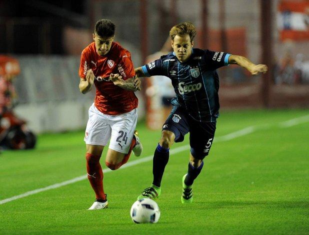 Emiliano Rigoni disputa el balón con Nery Leyes en el partido jugado anoche en Avellaneda.