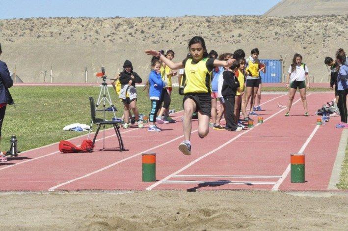 Una niña en plena competencia de salto en largo.