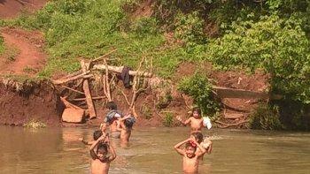 ninos cruzan a nado un arroyo para ir a la escuela