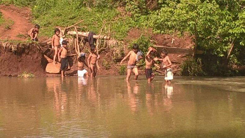 Niños cruzan a nado un arroyo para ir a la escuela