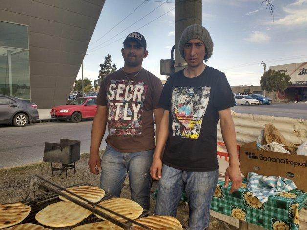 Santiago Castaño y Ariel Cruz venden productos panificados que elaboran en una parrilla.
