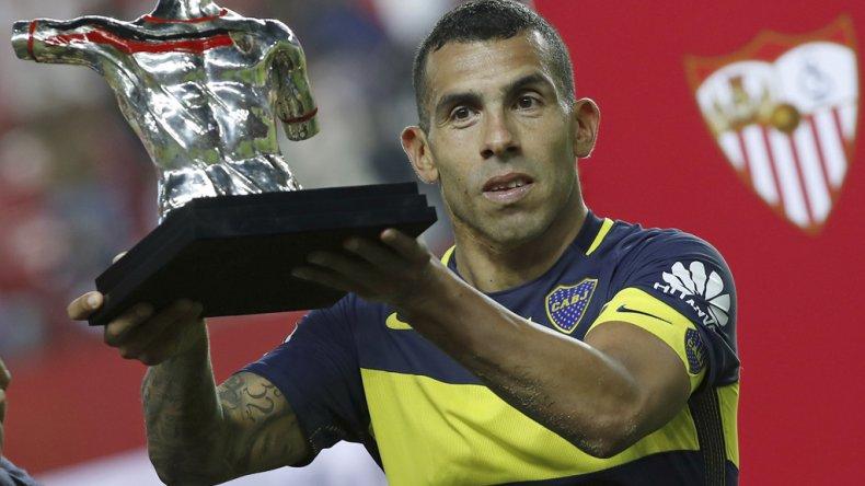 Carlos Tevez exhibe el trofeo que le ganó ayer Boca en un partido amistoso ante el Sevilla.