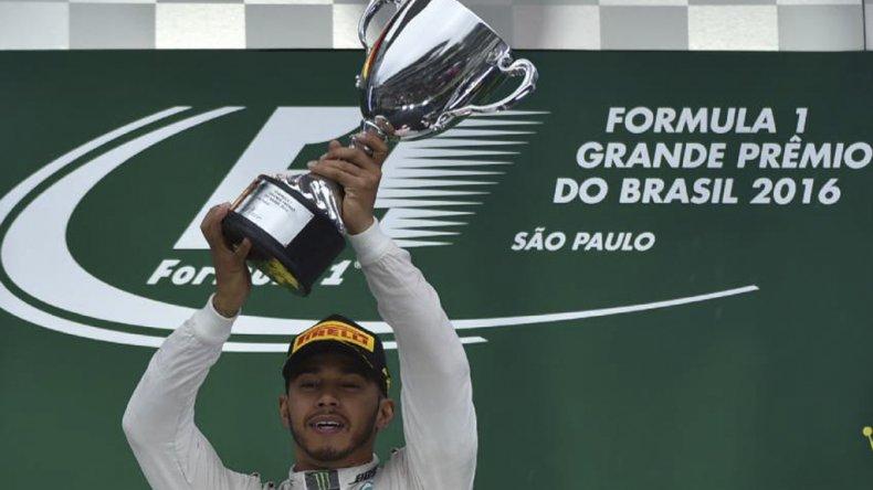 El inglés Lewis Hamilton levanta el trofeo que conquistó ayer en Brasil.