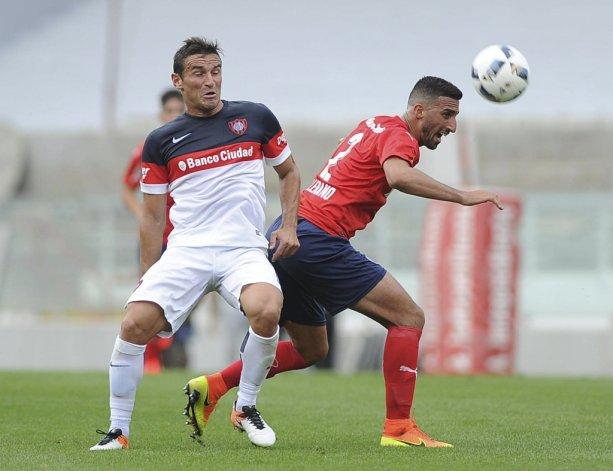 Hernán Pellerano disputa el balón con Gonzalo Bergessio ayer en Avellaneda.