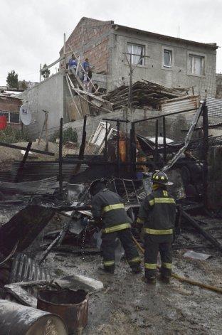 Los bomberos trabajan en el lugar donde la vivienda quedó reducida a escombros.
