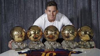 Lionel Messi posando con sus cinco balones que lleva ganados.