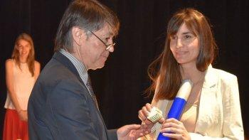 El rector Hugo Santos Rojas hace entrega del diploma a una de las nuevas profesionales graduadas en la Unidad Académica Caleta Olivia de la UNPA.