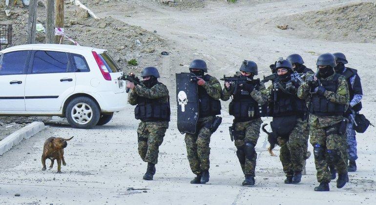 Las fuerzas especiales de la policía ingresan a la casa deshabitada en cuyo frente había quedado el cuerpo de Oscar Mansilla.