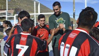 Diego Romero, pivote de Gimnasia y Esgrima, es saludado por chicos en una plaza del barrio La Floresta.