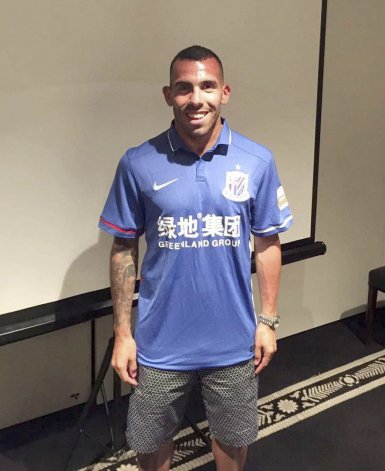 Carlos Tevez posa feliz con la camiseta de su nuevo club.